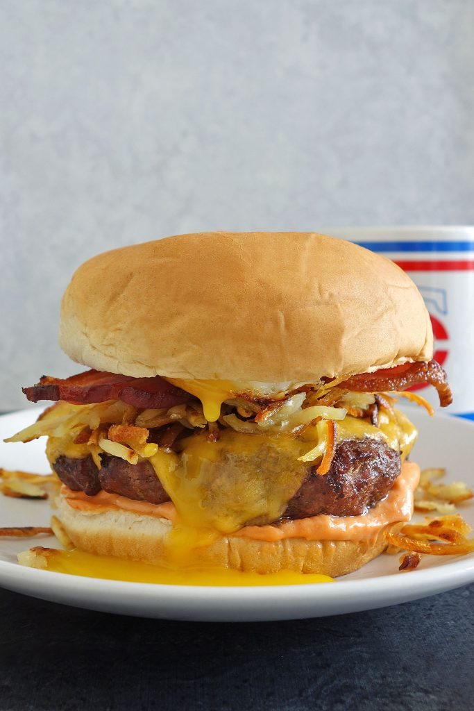 hangover burger recipe topped with hash browns, sunny side up egg, and bacon