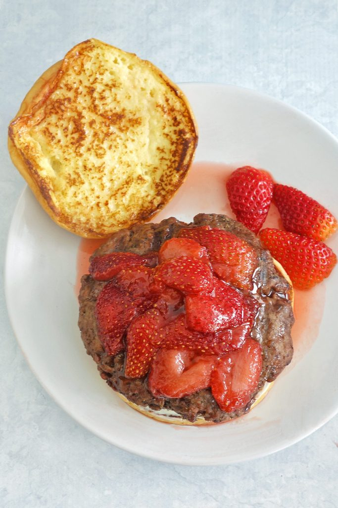 The strawberry french toast burger has a french toasted bun, cream cheese and is topped with strawberries.