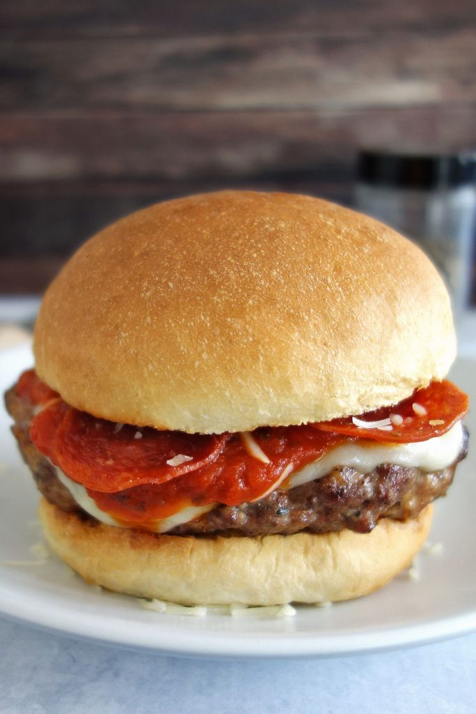 The pizza burger is a delicious Italian sausage burger topped with traditional pizza toppings like pepperoni mozzarella and parmesan cheese.